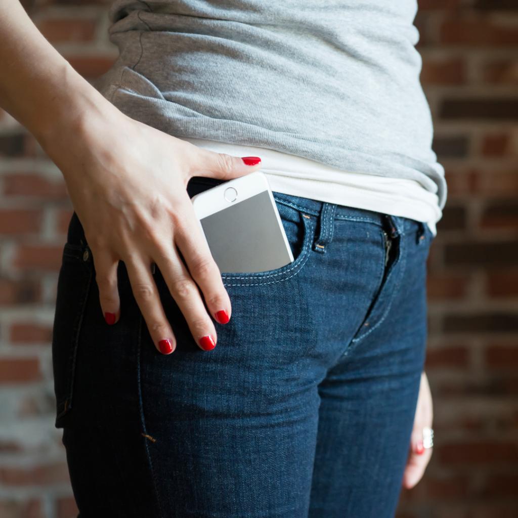 Ženska osoba stavlja telefon zaštićen zaštitnim folijama u prednji džep pantalona